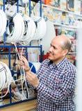 Man som väljer kabel i hushålllager royaltyfria foton