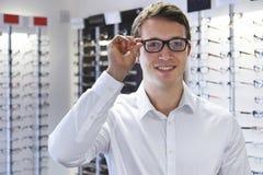 Man som väljer nya exponeringsglas på optiker arkivfoto