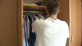 Man som väljer skjortan arkivfilmer