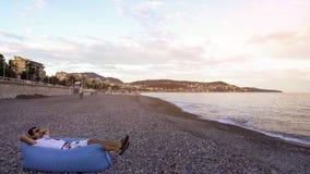 Man som vilar och tycker om sikten av medelhavet som ligger på luftsoffan på kust royaltyfria foton