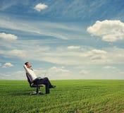 Man som vilar på det gröna fältet Arkivfoton