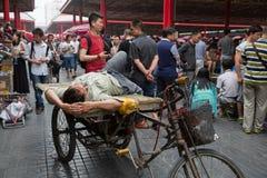 Man som vilar på en rickshaw av Panjiayuan den antika marknaden, Beij Arkivbilder