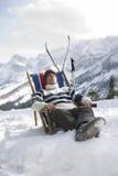 Man som vilar på Deckchair i snöig berg Royaltyfri Fotografi