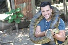 Man som visar affektion för en gigantisk orm royaltyfri bild