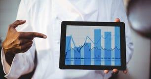 Man som visar den digitala minnestavlan som visar grafdiagrammet på skärmen arkivfoton