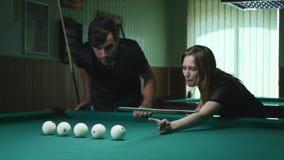 Man som visar hans flicka var att slå bollen - hälerirådgivning för ung kvinna på skyttepölboll, medan spela biljard arkivfilmer