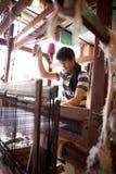 Man som väver matta på den traditionella trävävstolen Arkivfoto