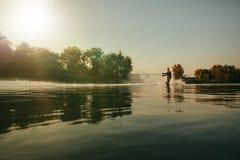 Man som wakeboarding på sjön på solnedgången Fotografering för Bildbyråer