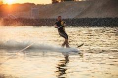 Man som wakeboarding på sjön på solnedgången Arkivfoto