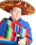 Man in Sombrero. A man wearing a sombrero, a colorful Mexican rug and carry a bottle of beer stock image