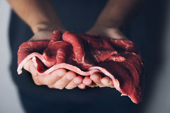 Man with some raw beefsteaks in his hands. Closeup of a young caucasian man with some raw beefsteaks in his hands Stock Image