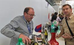 Kyiv Wine Festival by Good Wine in Ukraine. Man sommelier pours wine at Kyiv Wine Festival booth. Big festival of wine was organized by Good Wine company, 77 Royalty Free Stock Photo