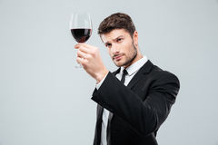 Man sommelier tasting and looking at red wine in glass. Concentrated young man sommelier tasting and looking at red wine in glass over white background Royalty Free Stock Photography