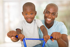 Man son bicycle. Portrait of african men helping son to ride a bicycle royalty free stock photography