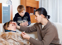 Man and son caring for sick woman Stock Photos