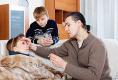 Man and son caring for unwell woman Stock Images