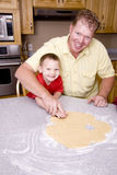 Man and son cutting cookies Royalty Free Stock Images