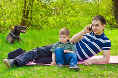 Man  with son and dog outdoors. Talking on the phone Stock Image