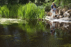 Man and son fishing together by lake Stock Photography