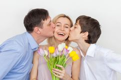 Man and son gives a bouquet of flowers to woman. Husband gives a gift to his wife. Mother`s day stock photo