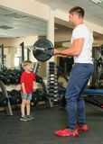 Man and son in the gym. Pope shows little son how to lift weights in the gym Royalty Free Stock Photos