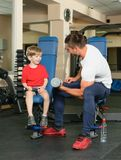 Man and son in the gym. Pope shows little son how to lift weights in the gym Royalty Free Stock Photo