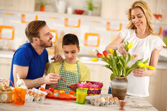 Man with son painting eggs while mother arranges tulips Royalty Free Stock Image