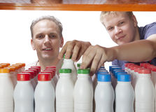 Man with the son select dairy products from a shelf in the shop. The men with the son select dairy products from a shelf in the shop Royalty Free Stock Images