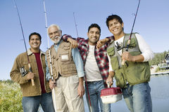 Man And Sons With Fishing Rods And Box. Portrait of happy senior men and sons with fishing rods and box Stock Photography
