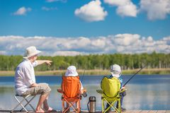 Man and sons sit on the pier. And fishing Royalty Free Stock Image