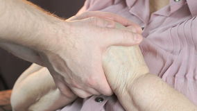Man soothes elderly woman during stress. Man holding the old wrinkled hands of elderly woman. Man soothes the elderly woman during stress. Close up stock video footage