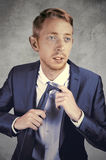 Man in a sophisticated dark blue suit fixing his tie. Stock Photos