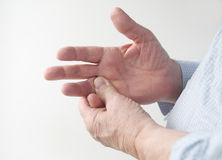Man with sore finger. A man rubs the pain in his finger stock photo