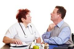 Man with sore throat seeing doctor. Elderly man with sore throat seeing a doctor stock image