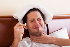 Man with sore throat. Young man with strong sore throat taking medicines Stock Photos