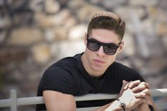 Man with sort hair leaning on banister. Wear sunglasses looking away Royalty Free Stock Photos