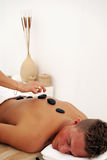Man in spa. A young man relaxes as he enjoys a luxurious spa treatment from a female masseuse Stock Photo