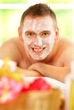 Man in spa. Happy man resting in sunny spa salon laying with facial mask Royalty Free Stock Photos