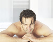 Man in spa. Attractive man laying down in bright modern spa environment smiling waiting for treatments Stock Photos