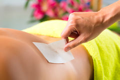 Man in Spa getting back waxed for hair removal Royalty Free Stock Photo