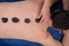 Man on a spa getting a hot stone massage. Stock Photo