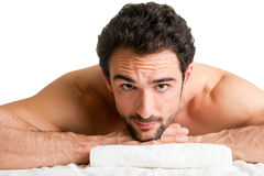 Man in a Spa. Man lying in a spa ready to get a massage, isolated in white Royalty Free Stock Photo