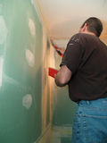 Man spackling new drywall. In a bathroom Royalty Free Stock Image