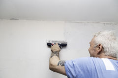 Man spackling a wall Stock Images