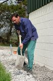 Man With A Spade. Shovelling and levelling gravel on a drainage path next to building royalty free stock photo