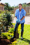 Man spade garden. Happy young man with a spade in home garden stock images