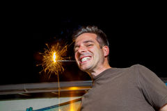 Man With Sparkler Between His Teeth. A man with a sparkler between his teeth and a cheesy grin smiles for the camera Royalty Free Stock Photography