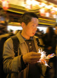 Man With Sparklers Burning in Hand. A man holds burning sparklers in his hand at a night market fair Royalty Free Stock Image