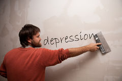 Man with a spatula deleting the word Depression. A man with a spatula deleting the word Depression Royalty Free Stock Photo
