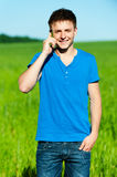 Man speaking on his mobile. Young smiley man speaking on his mobile. outdoors Stock Photos